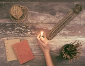 Woman Hand Lights A Incense Stick From A Buddha Holder On A Vintage Natural Wooden Surface With Book poster