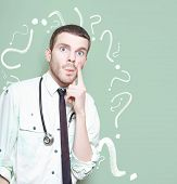 stock photo of punctuation marks  - Confused Healthcare Doctor Standing Looking Puzzled Against A Green Question Mark Background In A Depiction Of A Unknown Cure Or Medical Mystery - JPG