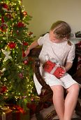 Little vintage girl in victorian eyelet dress looking at the christmas tree