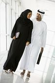 Middle Eastern Business Couple Walking Down Corridor