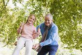 Grandparent Pushing Child On Swing