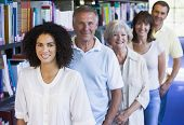 stock photo of 55-60 years old  - Five people in library standing by bookshelves  - JPG