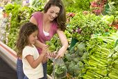 stock photo of department store  - Mother and daughter shopping for broccoli at a grocery store - JPG