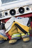 stock photo of fire truck  - Firefighting uniforms in front of a fire engine - JPG