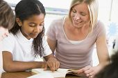image of student teacher  - Student in class reading book with teacher - JPG