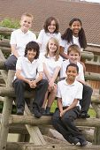 image of tweeny  - Seven students sitting on wooden structure outdoors - JPG