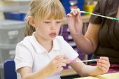 Portrait Of Child Putting Beads On Piece Of String In Classroom