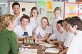 Teacher And Teen Pupils In Chemistry Lesson