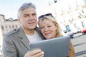 Pareja Senior con tableta digital en zona turística