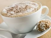 Cup Of Cappucino With An Amaretti Biscuit