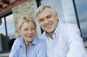 stock photo of villa  - Cheerful senior couple looking at camera - JPG