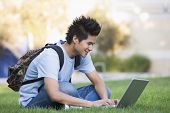 Man Outdoors Sitting On Grass With Laptop (Selective Focus)