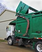 stock photo of trash truck  - truck pickingup dumpster full of trash - JPG