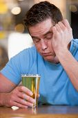 picture of saddening  - Innebriated man with glass of beer - JPG
