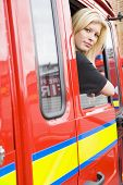 Firewoman Sitting In Fire Engine With Head Out Window