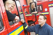 Firewoman Sitting In Fire Engine Talking To Fireman Standing Outside
