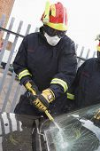 stock photo of crew cut  - Two firefighters cutting out a windshield after an accident - JPG