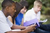 Four Students Outdoors Studying With One Checking Cellular Phone (Depth Of Field)