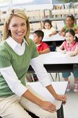 stock photo of student teacher  - Teacher in class with students in background  - JPG