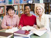 foto of 55-60 years old  - Three women sitting in library with books and notepads  - JPG