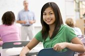 stock photo of hair integrations  - Female student with other students in classroom - JPG