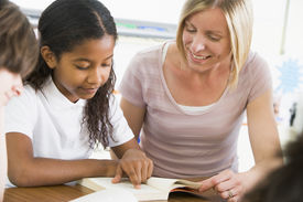 picture of student teacher  - Student in class reading book with teacher - JPG