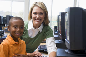 picture of student teacher  - Teacher sitting with student at computer terminal with students in background  - JPG