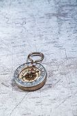 picture of cartographer  - Old compass on a cartographic map of mountains - JPG