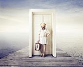 beautiful woman dressed with vintage clothing in front of a door in the middle of the sea
