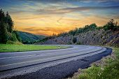 stock photo of curvy  - Landscape with curvy road at summer sunset - JPG