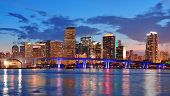 pic of skyscrapers  - Miami city skyline panorama at dusk with urban skyscrapers and bridge over sea with reflection - JPG