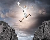 stock photo of gap  - Image of young businesswoman jumping over gap - JPG