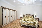 Luxurious bedroom with gilt double bed and wardrobe in classic style.