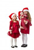 Two girls stand in a red dress in Santa Claus hats, one holding a baby boy