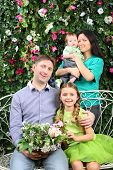 Family of four with bunch of flowers in garden near verdant hedge.