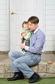 Father holds on hands crying baby, soothes and sits on steps near door.