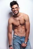 young topless man looking at the camera while holding his hand on his crotch and smiling. on light g