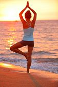 Yoga meditation woman meditating at beach sunset relaxing in yoga posture, tree pose, vrksasana. Rel