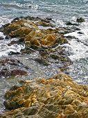 Foamy water washes over barren rocks