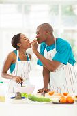 loving african husband feeding wife a piece of tomato while cooking