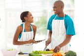 beautiful young african couple in home kitchen cooking