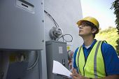 stock photo of electricity meter  - Maintenance worker reading meter of solar generation unit in Los Angeles - JPG