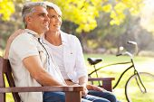 stock photo of bench  - beautiful elegant mid age couple daydreaming retirement outdoors - JPG