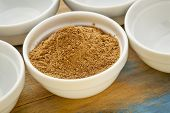raw organic dried camu camu fruit powder (Myciara Dubia) in a small ceramic bowl - rainforest superf