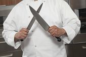 Midsection of male chef sharpening knives in commercial kitchen