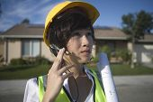 Young female solar panel worker with blue print wearing headset outdoors