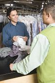 Male laundry owner showing dry cleaned shirts to customer at counter