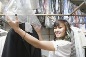 Portrait of smiling young woman putting plastic to dry cleaned coat in laundry