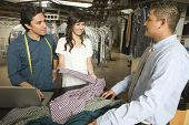 Laundry owners showing dry cleaned clothes to customer at counter in laundry