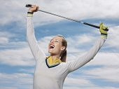 stock photo of v-day  - Happy female golfer holding club against sky - JPG